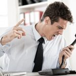 Angry young Businessman sitting in the office and screaming on the phone.